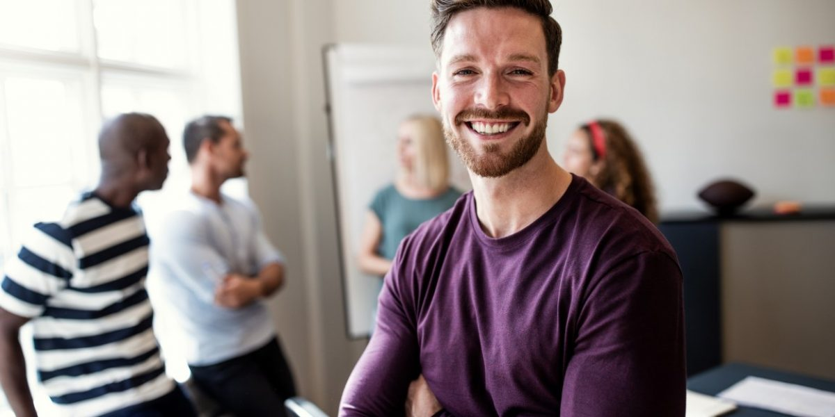 Smiling young designer standing confidently with his arms crossed after a boardroom meeting with colleagues standing in the background