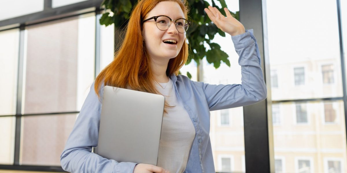 young-caucasian-woman-in-blue-shirt-in-bright-office-greets-colleagues-and-partners-in-the-office_t20_E0bVKX (Groot)